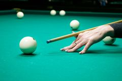 Female hand holds a cue for striking the white cue ball. Woman p stock photos