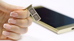 A female hand holds a dual SIM card slot. Nano SIM and memory card with ejector pin and tray for Touchscreen phone Royalty Free Stock Photography