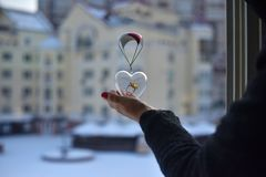 A female hand holds a glass transparent heart with a big ring inside. Flown into her window on a small parachute against the background of urban houses stock photography