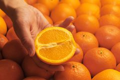 A female hand holds half an orange. Close-up Stock Image