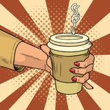 Female hand holds hot cardboard cup with coffee comic style. During a working break she drinks energy drink. Vintage pop art retro vector illustration