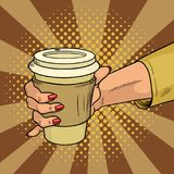 Female hand holds hot cardboard cup with coffee comic style. During a working break she drinks energy drink. Vintage pop. Art retro vector illustration. EPS 10 Royalty Free Stock Photo