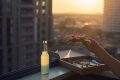 A female hand holds a huge piece of pizza on sunset and city background. Concept royalty free stock photo