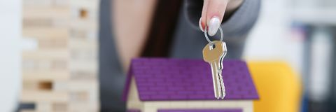 Female hand holds the key to the lock in. The hand against the backdrop of the toy house sale purchase lease concept real estate services on the market Royalty Free Stock Photo