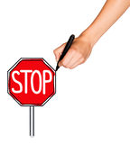 A female hand holds marker and draws stop sign. A female hand holds black marker and draws red stop sign. Isolated on white background Stock Image