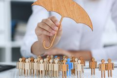 The female hand holds a miniature umbrella. In the hand of the topic of liability insurance Royalty Free Stock Image