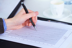Female hand holds pen over graph Royalty Free Stock Image