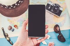 A female hand holds the phone over things for travelTravel plan, trip vacation, tourism mockup Instagram looking image of travelli Stock Image