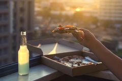 A female hand holds a piece of pizza on sunset and city background. A female hand holds a huge piece of pizza on sunset and city background. Concept royalty free stock photos