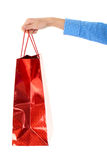 Female hand holds red gift bag, isolated Royalty Free Stock Photo
