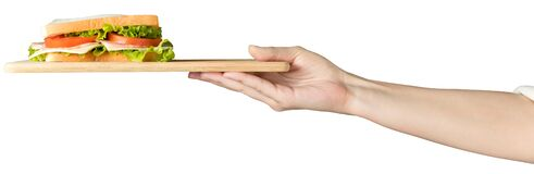 Female hand holds a sandwich with fresh herbs on a wooden tray