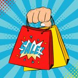 Female hand holds shopping bags. Cartoon sale banner in pop art style on dots halftone background. Vector. Female hand holds shopping bags. Cartoon sale banner Royalty Free Stock Image