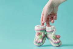 Female hand holds small baby shoes Royalty Free Stock Images