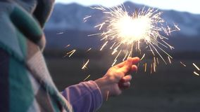 Female hand holds sparkler on a background of snowy mountains, beautiful sunset stock video