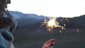 Female hand holds sparkler on a background of snowy mountains, beautiful sunset stock video footage