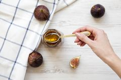A female hand holds a spoon with fig jam, top view. From above royalty free stock photos