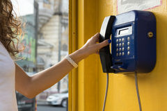 Female hand holds up the phone. Calling from city payphones stock photo