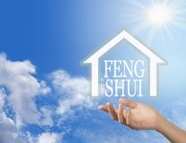 Let the Enlightened Wisdom of Feng Shui into your Home. Female hand with a house shape containing the words FENG SHUI floating above against a blue sky royalty free stock photos