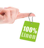 Female hand with hundred percent linen tag Stock Images