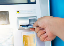 Female hand inserting ATM card into bank machine to withdraw mon. Female hand inserts credit card into the ATM and withdraws money in very shallow focus Royalty Free Stock Images
