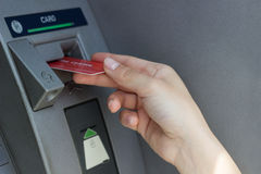 Female hand inserts credit card into the ATM Royalty Free Stock Image