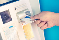 Female hand inserting ATM card into bank machine to withdraw mon. Female hand inserts credit card into the ATM and withdraws money n very shallow focus Stock Photos