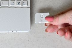 A female hand inserts a white compact SD card into the corresponding input in the side of the white netbook. Woman uses modern te. Chnologies to store memory and royalty free stock images