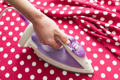 Female hand ironing clothes top view during housework. Close-up of maid hand ironing clothes on ironing board at home. Royalty Free Stock Images
