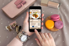 Female hand with jewelry holding phone with app delivery food Royalty Free Stock Photos