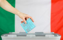 Female hand keeps ballot over ballot box. Italian flag in the ba. Female hand keeps ballot over ballot box. Translation from Italian-Election to the Senate of Stock Photo
