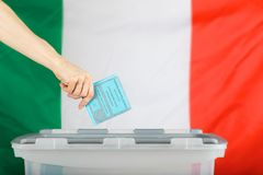 Female hand keeps ballot over ballot box. Italian flag in the ba. Female hand keeps ballot over ballot box. Translation from Italian-Election to the Senate of Stock Photography