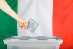 Female hand keeps ballot over ballot box. Italian flag in the ba. Female hand keeps ballot over ballot box. Translation from Italian. Election to the Chamber of Royalty Free Stock Photography