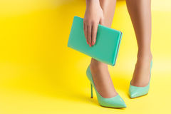 Female hand keeps portable turquoise bag on yellow background; Stock Photos