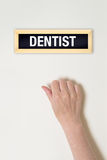 Female hand is knocking on Dentist door Royalty Free Stock Image