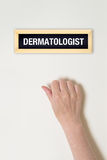 Female hand is knocking on Dermatologist door Royalty Free Stock Images