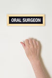 Female hand is knocking on Oral surgeon door Stock Photography