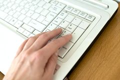 Hand on laptop keyboard stock photos
