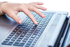 Female hand on laptop keyboard Stock Images