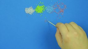 Female hand lays out patterns of beads on a blue background with a wooden stick. Close-up. Handmade stock video footage