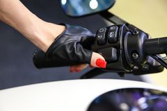 Female hand in a leather glove presses the button on the handlebar of the motorcycle royalty free stock image