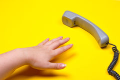 Female hand lies next to the telephone receiver on the wire. On a yellow background Royalty Free Stock Image