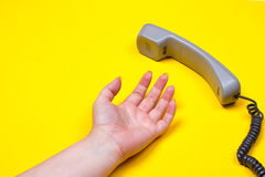 Female hand lies next to the telephone receiver on the wire. On a yellow background Stock Image