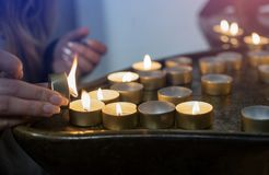 Female hand lighting candles in the chapel. Burning faith candle in a church Stock Images