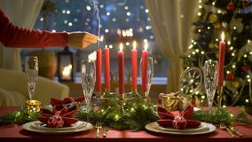 Female hand lights christmas candles. Festive red table setting with garland. Fale hand lights christmas candles. Festival red table setting with garland and stock footage