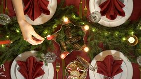 Female hand lights christmas candles. Festive red table setting with garland. Top view stock footage
