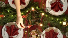 Female hand lights christmas candles. Festive red table setting with garland. Top view stock video footage