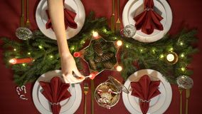 Female hand lights christmas candles. Festive red table setting with garland. Top view. Slow motion stock footage