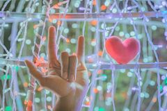 Female hand with a little red heart shape pillow on decorate colorful light bulbs. In garden stock photo