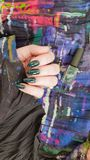 Female hand with long nails holds a bottle nail polish. Female hand with long nails holds a bottle with a bright nail polish royalty free stock images
