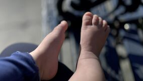 Female hand lovingly caressing the foot of her baby